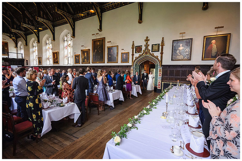 All the wedding guests standing and appluading entrance of Bride and Groom in main hall of St Johns College wedding reception