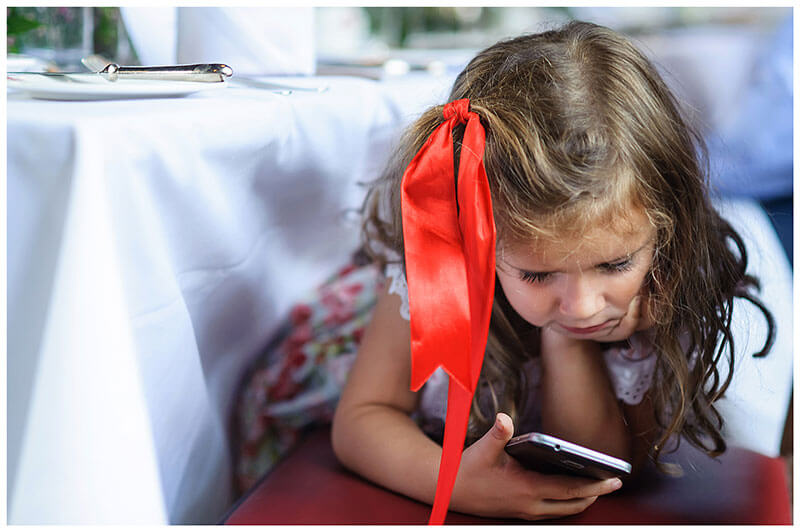 small girl with red ribbon in hair playing on phone
