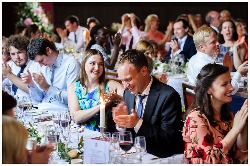 wedding guests laughing and applauding speeches wedding reception