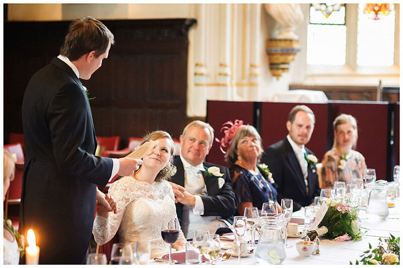 Bride holds grooms hand as he gives his speech