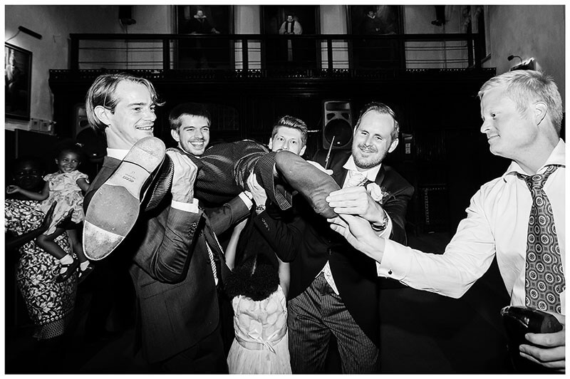Men carrying groom pulling on his sock during wedding reception