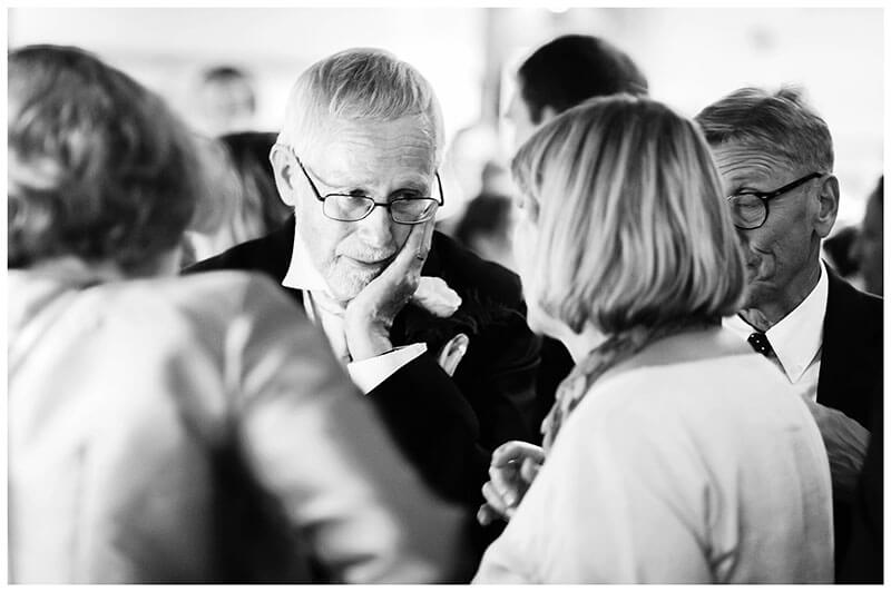 Old gentleman listening to lady talk in bar wedding reception