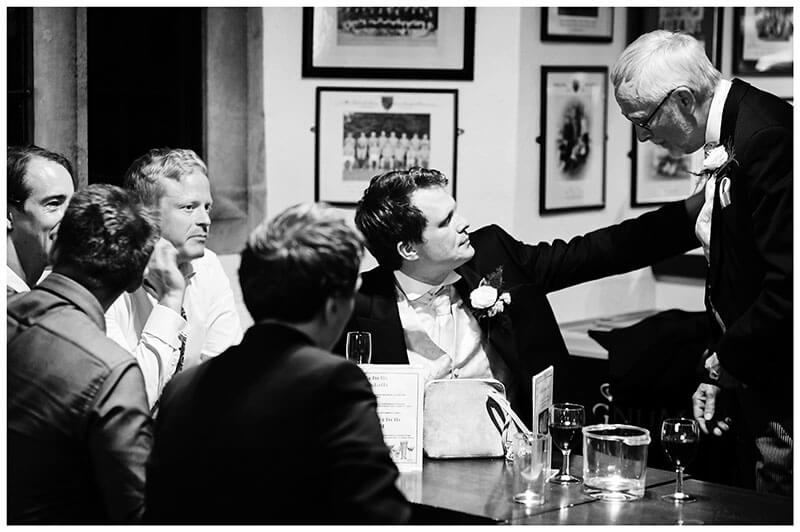 groom touches fathers arm while in conversation in St Johns College bar