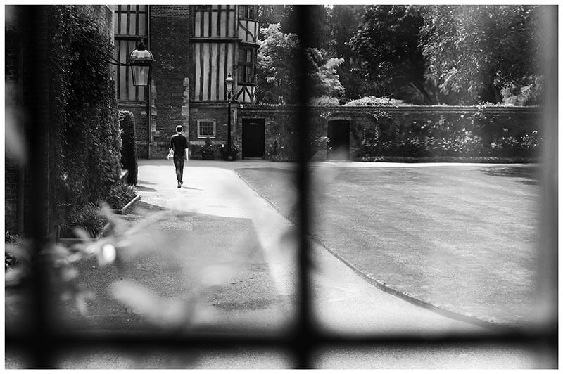 Groom viewed through window walking through Queens college grounds