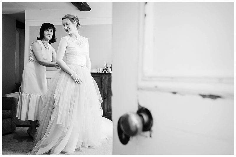 Bride helped by her mother in to her wedding dress