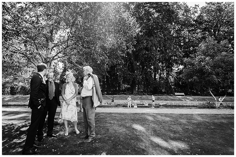 Wedding Guests talking to groom in gardens of Queens College Cambridge before ceremony