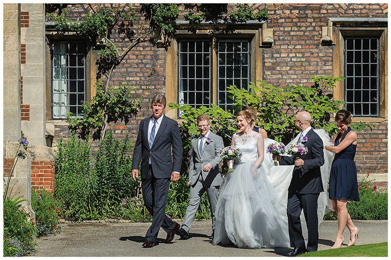 Bridesmaids holding dress as wedding party escort bride to ceremony at Queens College Cambridge