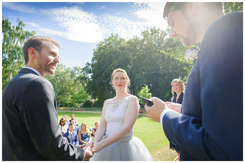 Bride groom look at officiante during wedding blessing ceremony in gardens of Queens College cambridge Gardens