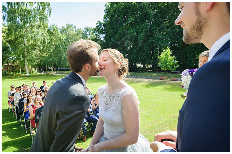 Bride groom about to kiss during wedding blessing ceremony in Queens College cambridge Gardens