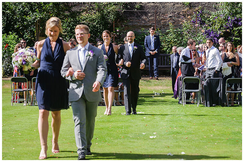 Guests watch as wedding party depart after ceremony in Queens College Gardens