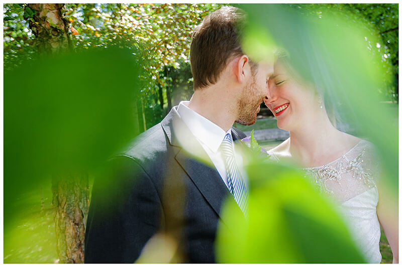 Bride groom have a romantic moment under an tree in Queens College Cambridge