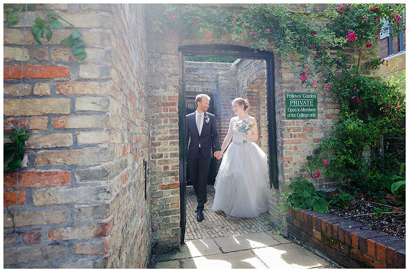 Bride groom in door way that leads to Queens College Fellows gardens