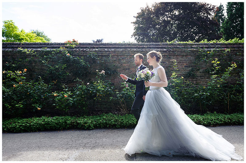 Bride groom walking next to wall cover in rose bushes in Queens College Cambridge Gardens
