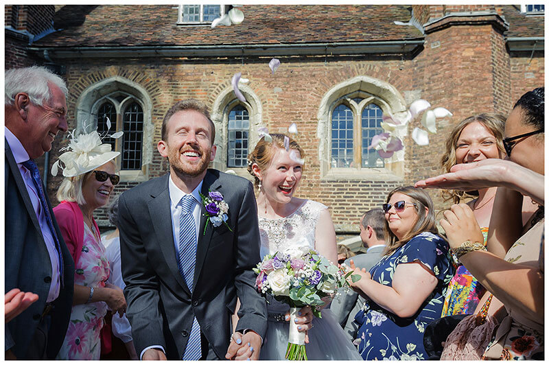 Smiling bride groom eyes closed rose confetti being thrown