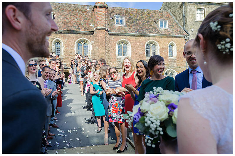 Wedding guests appluading bride and groom after confetti throwing