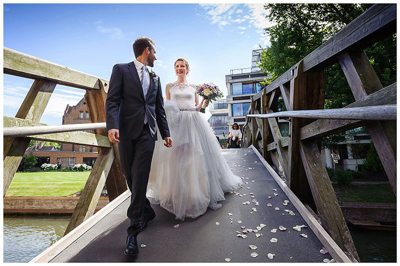 Groom looking back at smiling bride as they walk over Mathematical Bridge in Queens college Cambridge