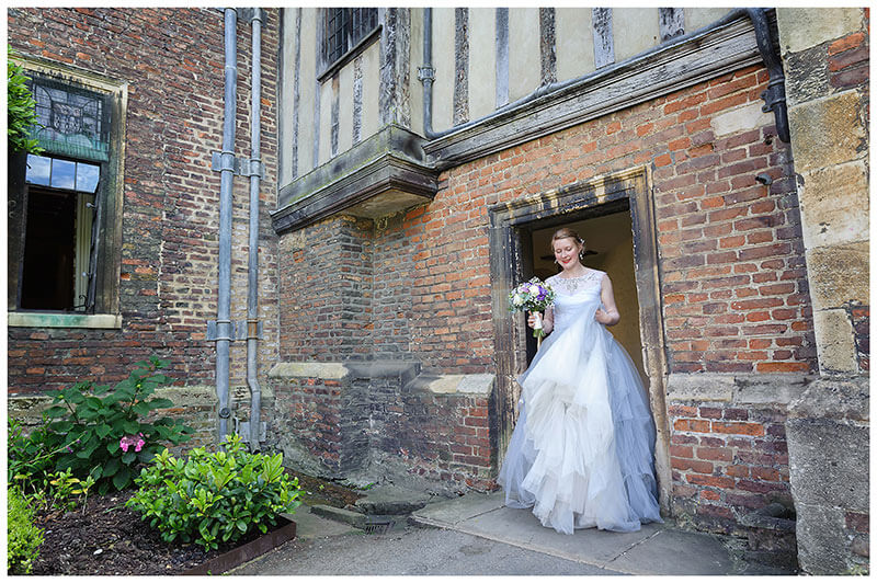 Bride walking through arch door way holding dress and bouquet