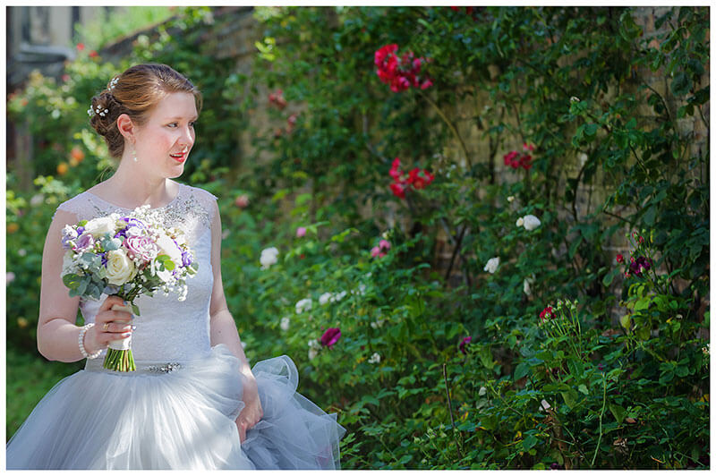 Bride in front of rose bushes holding her bouquet