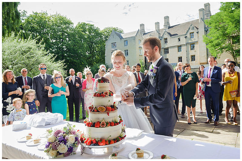 Bride groom cutting 4 tier wedding cake all their guest behind them