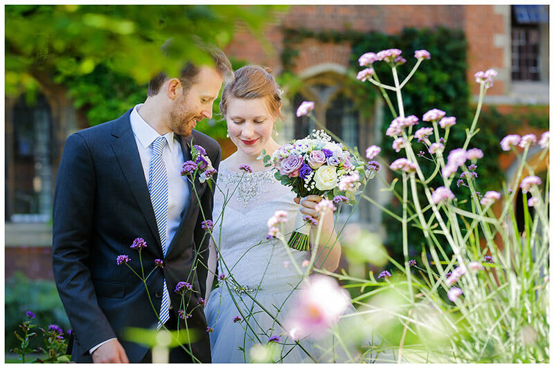 groom leads his bride as she hold her bouquet through purple wild flowers of Queens Colelge Cambridge