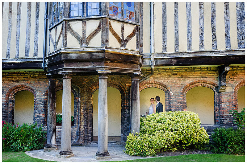 Bride leads groom through the cloisters of Queens College Cambridge