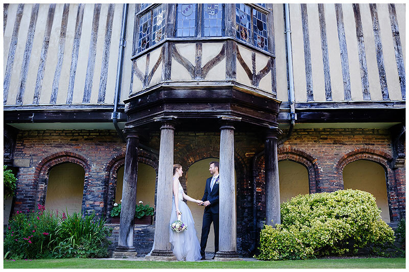 Groom takes brides hand as they stand amounst wooden pillars of Cloister Court Queens College Cambridge