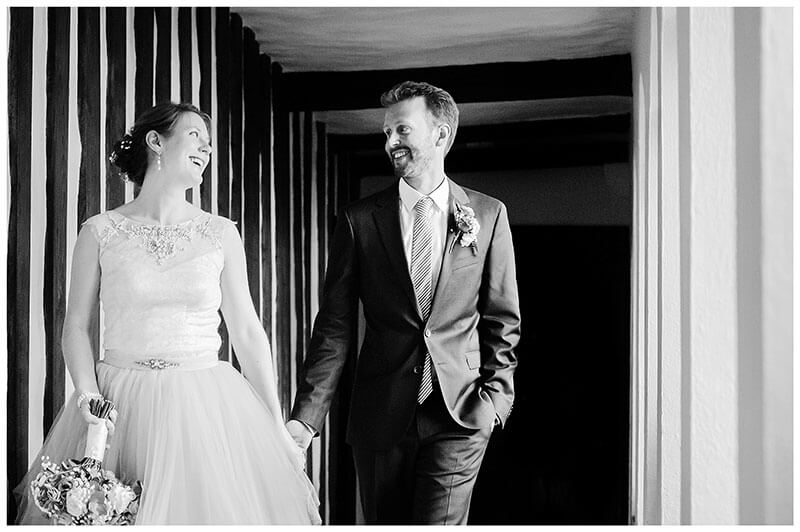Smiling bride groom holding hands as they walk through cloister at Queens College Cambridge