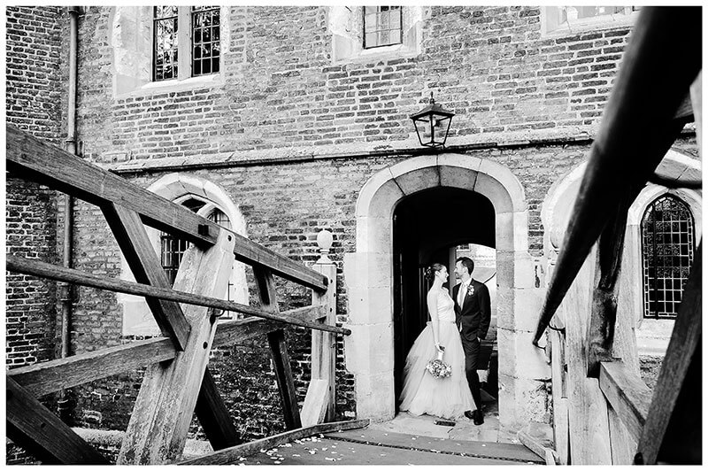 Bride groom embrace in archway next to Mathematical bridge Queens college cambridge