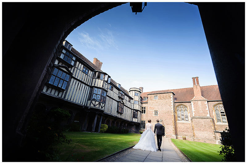 Bride groom walking away through arch holding hands in Queens College Cloister Court