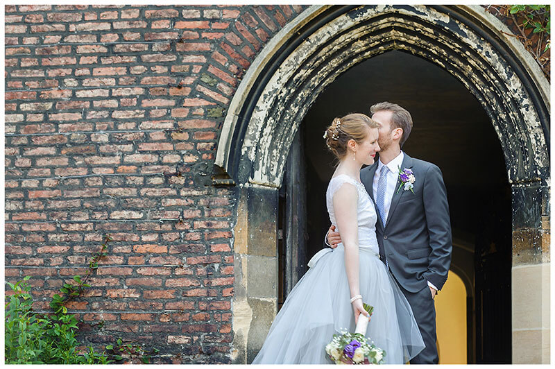 groom embraces bride and kisses her cheek in front of arch at Queens college wedding blessing
