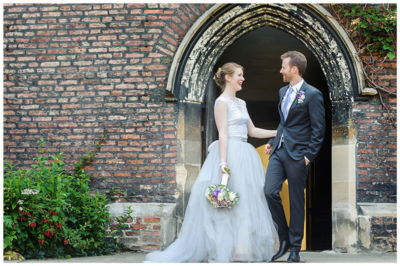Bride groom laughing in front of passage arch at Queens college wedding blessing