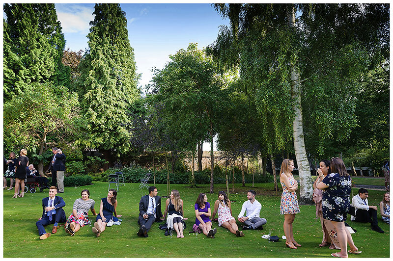 Wedding guests sat on lawns at Queens college wedding blessing