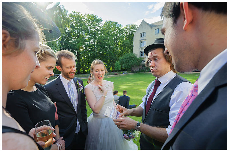 Magician pulls face as he magics money in front of bride groom guests at Queens college wedding blessing