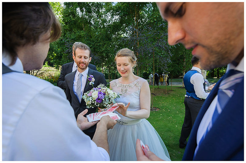 Bride picks card from magician pack as guest looks at his own card