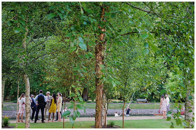 Wedding guests in gardens of Queens college during wedding blessing