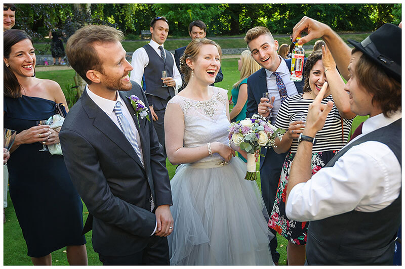 Bride groom laugh surrounded by guests as magician makes Grooms playing card appear in schweppes tonic bottle at Queens college wedding blessing