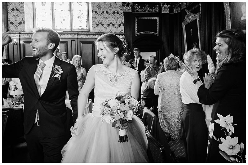 Groom punches air as bride groom walk through wedding dinner reception in Old Hall Queens College
