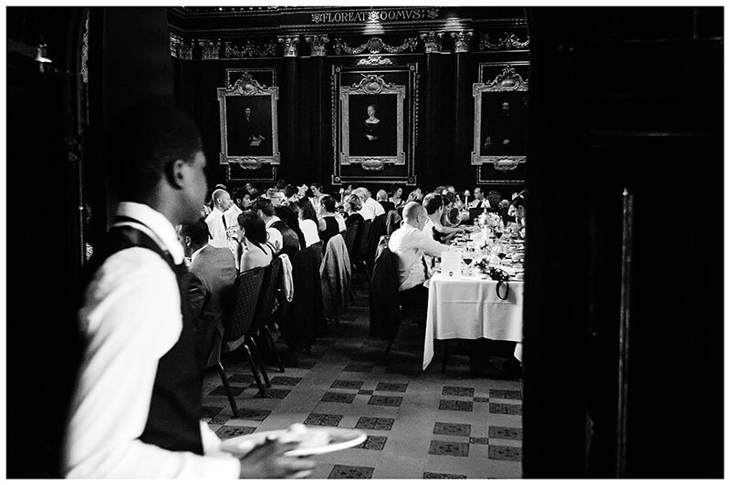 Waiter takes plates of food in to Queens College Old Hall for Queens college wedding blessing dinner