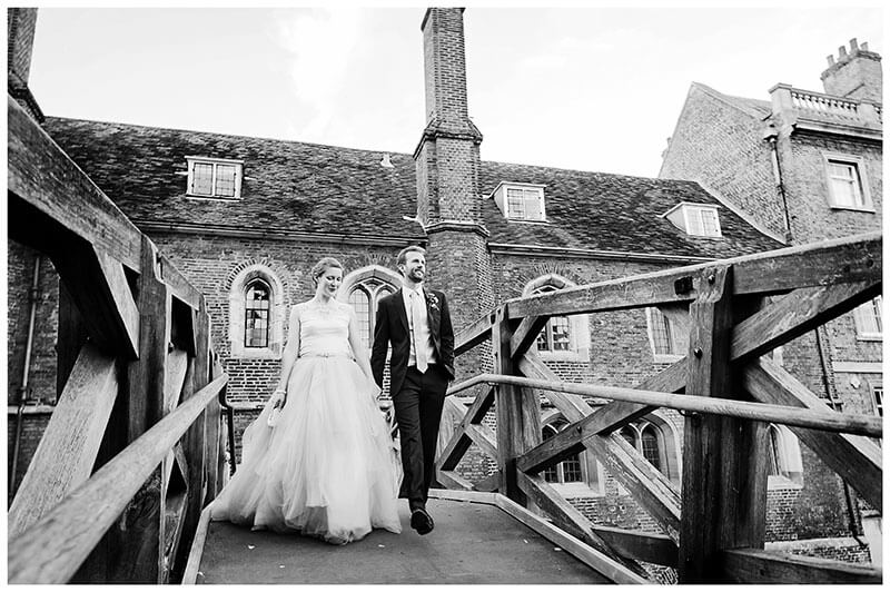 Bride groom walk hand in hand across Mathematical Bridge at Queens college after wedding blessing