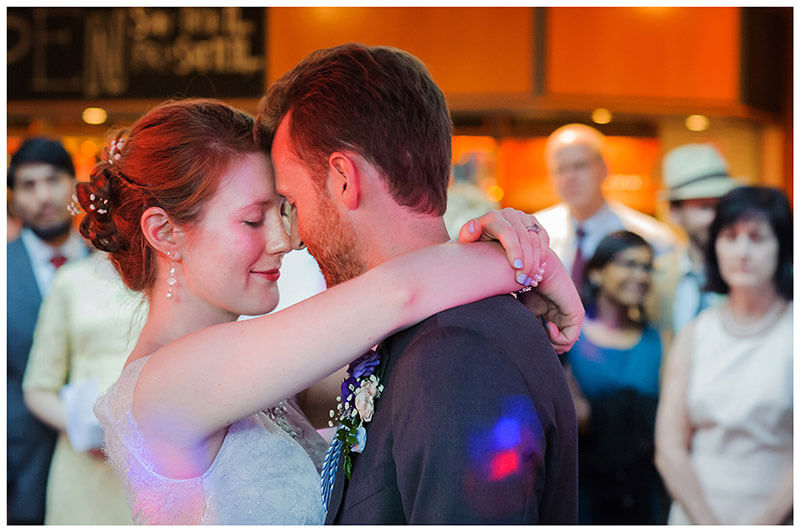 Bride wraps her arms around Grooms neck diruing first dance at Queens college wedding blessing