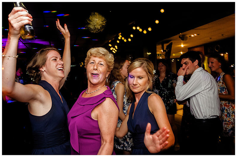 two bridesmaid sisters dancing with their mother at Queens college wedding blessing evening party