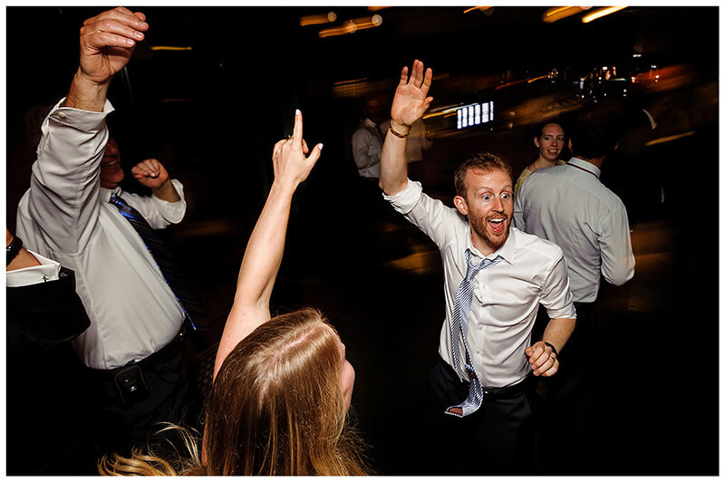 Groom and guests waving their arms in the air during evening party during Queens college wedding blessing