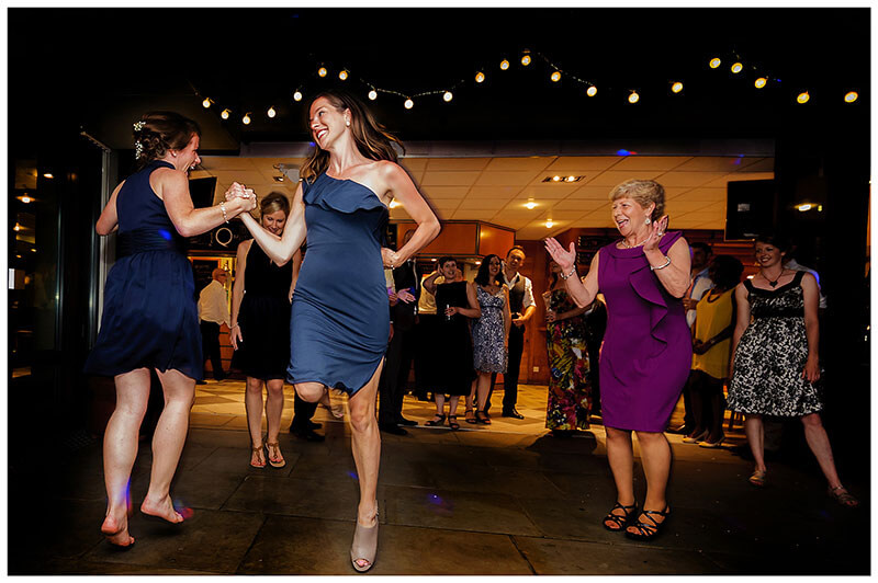 Ladies enjoying energetic dancing on the dance floor during Queens college wedding blessing evening party