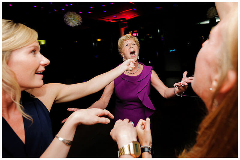 Lady singing into pretend microphone whilst on dance floor at Queens college wedding blessing