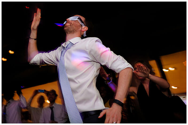 Groom wearing lit glasses on dance floor at Queens college wedding blessing