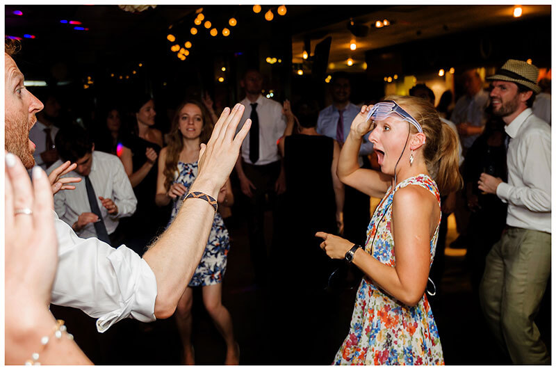 Lifting lit glasses look of suprise on dance floor at Queens college wedding blessing