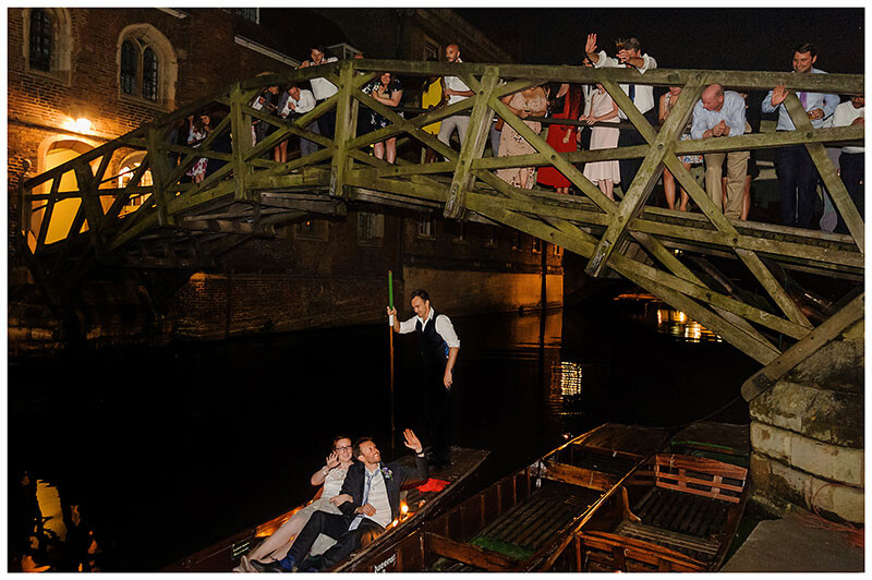 Bride groom sitting in punt on river Cam waving good night thier wedding guests standing on Queens College mathematical Bridge as they depart