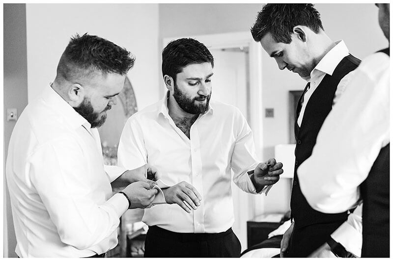 Groomsmen helping the groom get ready by fitting his cufflinks at Wentworth Club