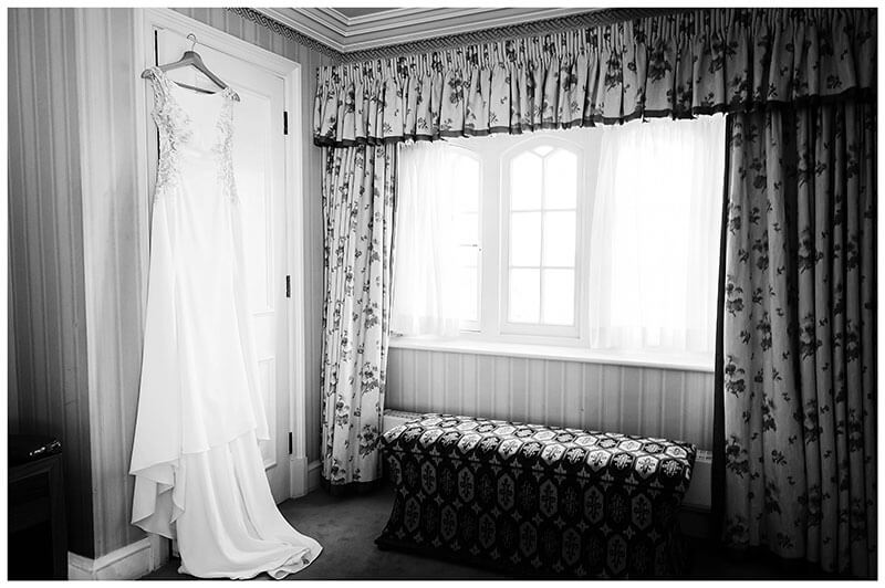 Brides dress hanging from door next to window at Wentworth Club