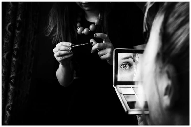 Eye of the bride reflected in small hand held mirror with make up artists hands in background holding mascara brush